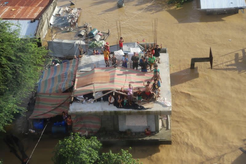 People stand on a roof of a building after Typhoon Vamco resulted in severe flooding, in the Cagayan Valley region