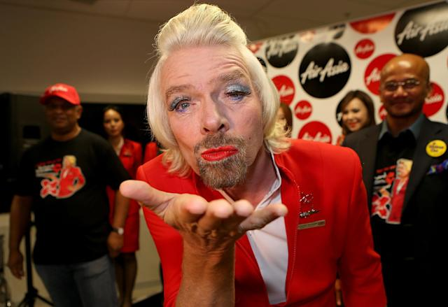 PERTH, AUSTRALIA - MAY 12: Sir Richard Branson blows a kiss before boarding his flight to Kuala Lumpur at Perth International Airport on May 12, 2013 in Perth, Australia. Sir Richard Branson lost a friendly bet to AirAsia Group Chief Executive Officer Tony Fernandez after wagering on which of their Formula One racing teams would finish ahead of each other in their debut season of the 2010 Formula One Grand Prix in Abu Dhabi and that the loser would serve as a female flight attendant on board the winner's airline. (Photo by Paul Kane/Getty Images)