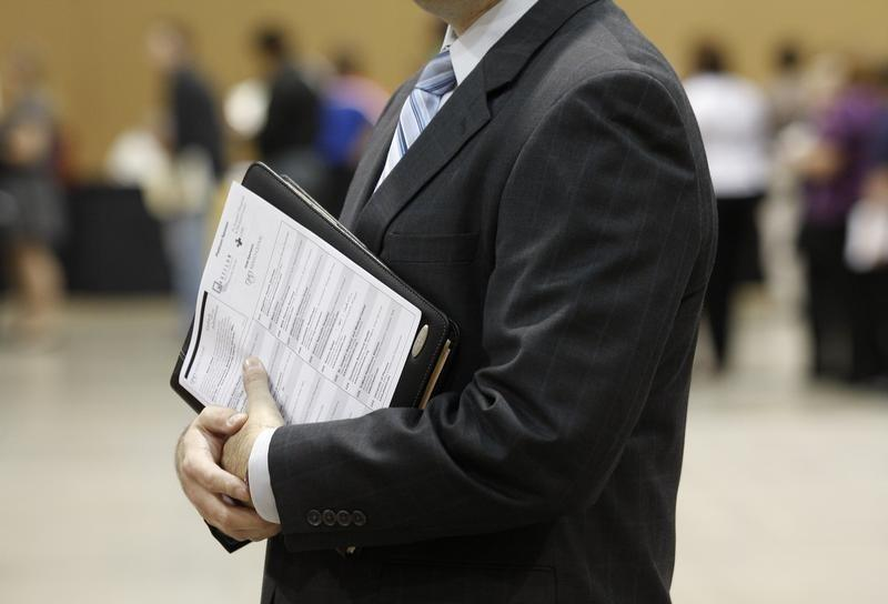 A job seeker holds his binder filled with resumes at the Phoenix Convention Center in Phoenix, Arizona