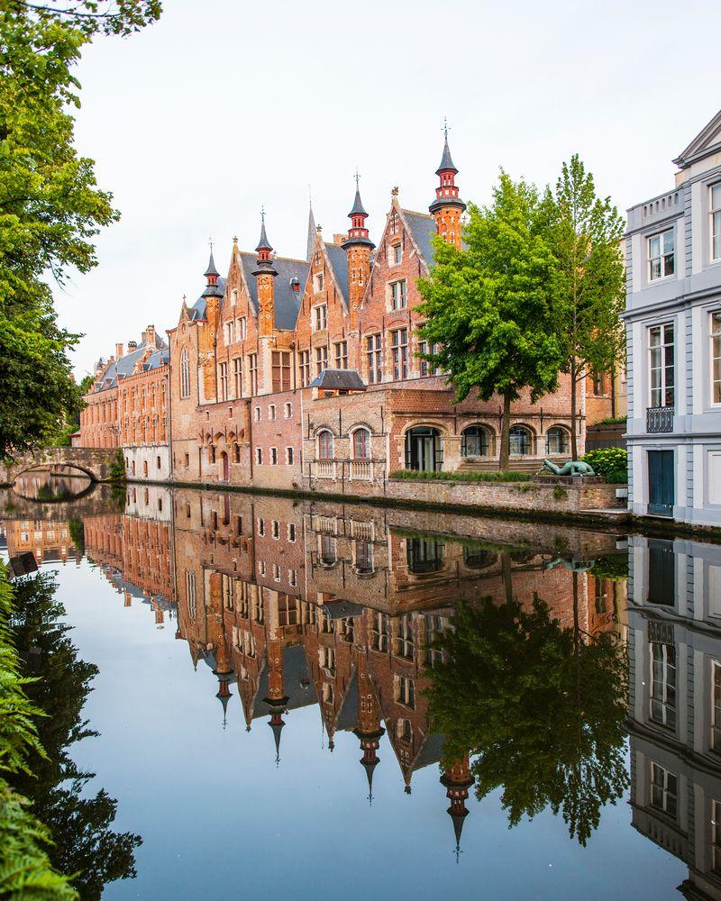 Charming canals encircle the Belgian town of Bruges. | Neil Emmerson / robertharding/Getty Images