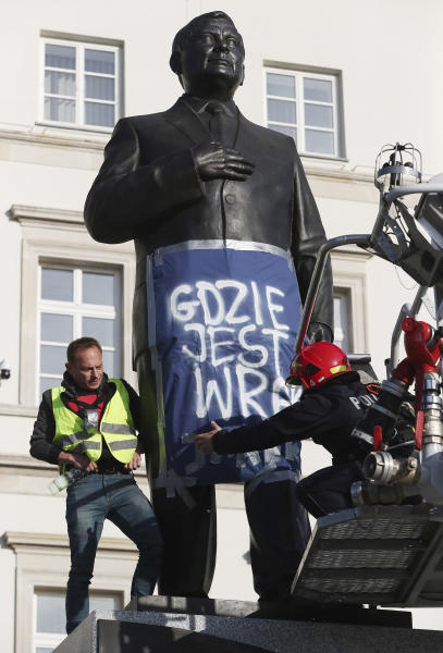 A man stands on a monument to Poland's late president Lech Kaczynski in downtown Warsaw, Poland, Friday, Oct. 11, 2019. He wrapped it in a banner reading 'Where is the Wreckage?' of the plane that crashed in 2010 in Russia, killing the president. Just two days ahead of parliamentary elections, this is criticism of the ruling Law and Justice party, led by the late president's twin Jaroslaw Kaczynski, which has vowed to bring the wreckage back from Russia, where it remains. (AP Photo/Czarek Sokolowski)