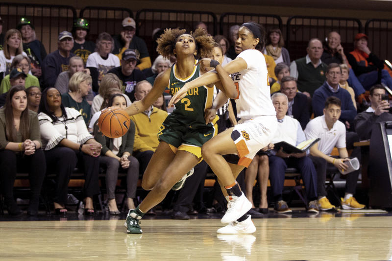 Baylor guard DiDi Richards (2) drives the basketball while under defensive pressure from Oklahoma State guard Lauren Fields (23) during the second half of an NCAA college basketball game in Stillwater, Okla., Saturday, Feb. 15, 2020. (AP Photo/Brody Schmidt)