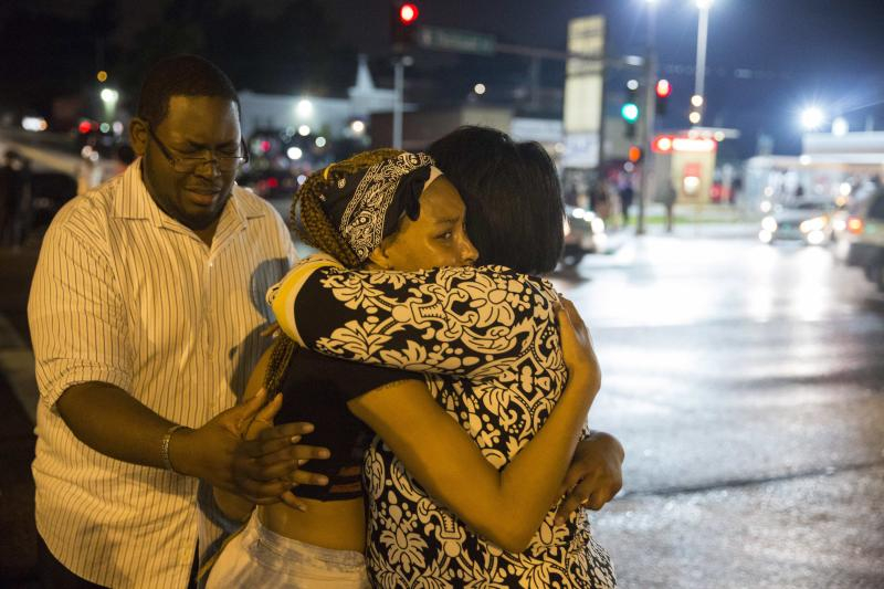 Demonstrators weep on each others shoulders as masked individuals break into a store, during on-going demonstrations to protest against the shooting of Michael Brown, in Ferguson, Missouri, August 16, 2014. Protesters in Ferguson said late on Friday on Twitter that police had fired tear gas at a crowd protesting over the police shooting death of Brown, an unarmed black teen. The reported outbreak late Friday evening came after almost a week of nighttime clashes between local police and protesters saw a 24-hour break as those police forces were replaced by state police led by an African-American captain. REUTERS/Lucas Jackson (UNITED STATES - Tags: CIVIL UNREST CRIME LAW)