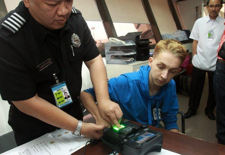 Thomas van Beersum has his fingerprint taken at the immigration office of Manila Airport on August 6, 2013