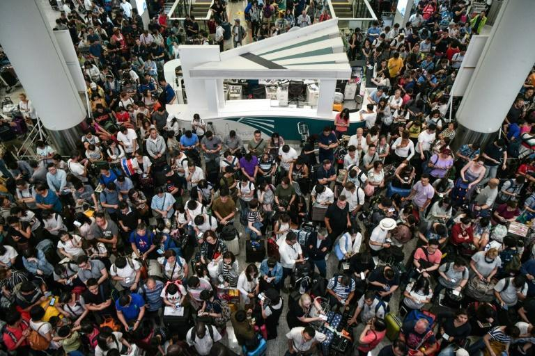Travellers wait in the terminal of Hong Kong's international airport after a train service linking it to the city was cancelled due to pro-democracy protesters (AFP Photo/Anthony WALLACE)