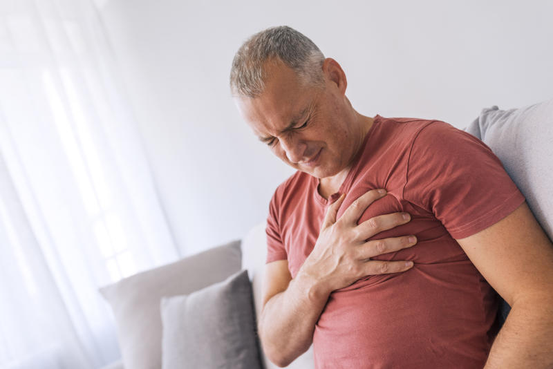 Severe heartache, man suffering from chest pain, having heart attack or painful cramps, pressing on chest with painful expression. Photo of Mature man suffering from chest pain at home during the day.