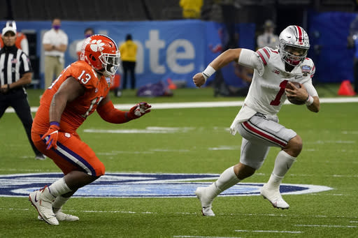 Ohio State quarterback Justin Fields runs past Clemson defensive tackle Tyler Davis during the first half of the Sugar Bowl NCAA college football game Friday, Jan. 1, 2021, in New Orleans. (AP Photo/John Bazemore)
