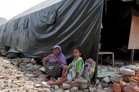 A child and her mother sit near their temporary shelter after their houses were demolished last year, in Luar Batang area in Jakarta, Indonesia April 18, 2017. REUTERS/Beawiharta