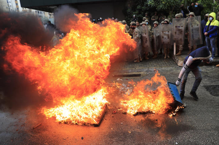 A protester sets a garbage container on fire in front of Lebanese army soldiers, during a protest against deteriorating living conditions and strict coronavirus lockdown measures, in Tripoli, north Lebanon, Thursday, Jan. 28, 2021. Violent confrontations between protesters and security forces in northern Lebanon left a 30-year-old man dead and more than 220 people injured, the state news agency said Thursday. (AP Photo/Hussein Malla)