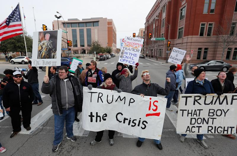 Protestors hold signs in a crosswalk in downtown Fort Worth, Texas, Monday, Feb. 18, 2019. People gathered on the Presidents Day holiday to protest President Donald Trump's recent national emergency declaration. (AP Photo/LM Otero)