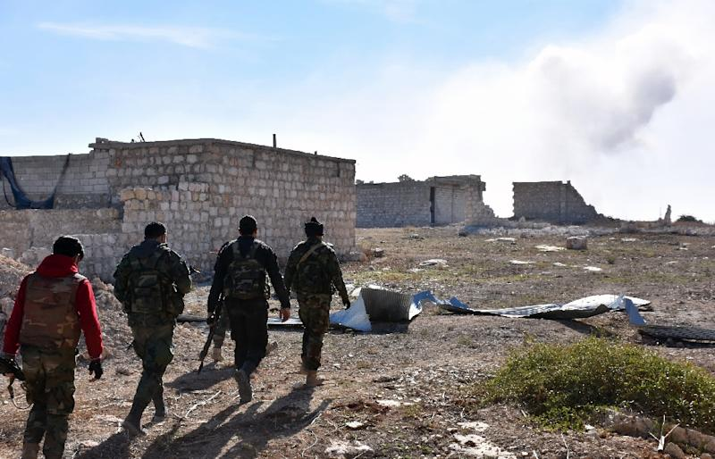 Syrian pro-government forces walk past damaged houses as they approach the Baeedin district in eastern Aleppo, near Masaken Hanano, on November 23, 2016