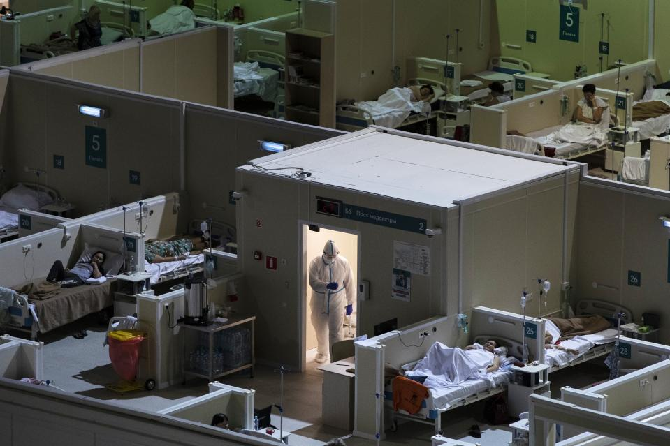 A medical worker walks next to patients in the treatment hall of a temporary hospital for coronavirus patients in the Krylatskoye Ice Palace in Moscow, Russia.
