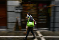 A woman wears a face mask to protect aginst coronaviris, while walking along a street during an autumn day, in Pamplona, northern Spain, Saturday, Oct. 3, 2020. (AP Photo/Alvaro Barrientos)