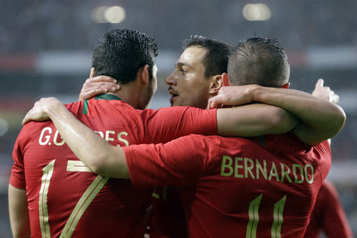 Portugal's Cedric Soares, celebrates with his teammates Portugal's Goncalo Guedes, left and, Portugal's Bernardo Silva after Silva scored the opening goal for his team during a friendly soccer match between Portugal and Algeria in Lisbon, Portugal, Thursday, June 7, 2018. (AP Photo/Armando Franca)