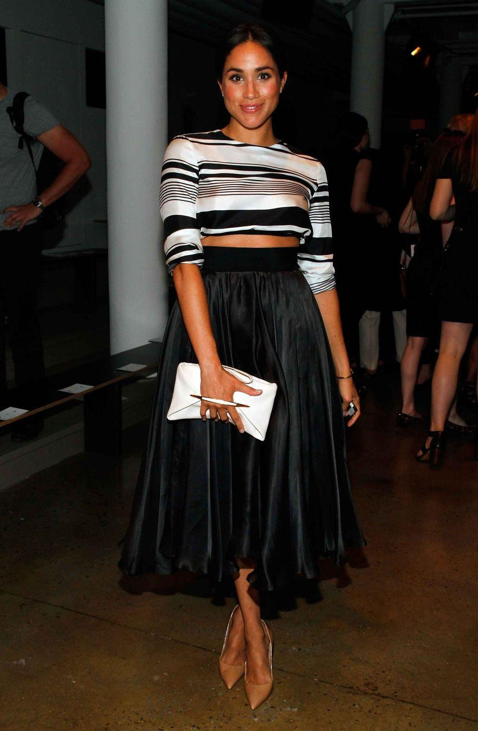 <p>Markle wears a tea-length black skirt and striped top while attending the Peter Som fashion show during Mercedes-Benz Fashion Week.</p>