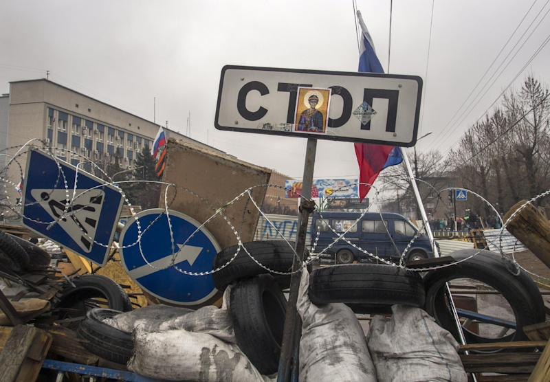 """Russian national flags fly above barricades with a road sign """"Stop"""" with an Orthodox icon in front of an entrance of the Ukrainian regional office of the Security Service in Luhansk, 30 kilometers (20 miles) west of the Russian border, Ukraine, Thursday, April 10, 2014. Ukrainian Interior Minister Arsen Avakov said Wednesday that the standoff in Luhansk and the two neighboring Russian-leaning regions of Donetsk and Kharkiv must be resolved within two days. (AP Photo/Igor Golovniov)"""