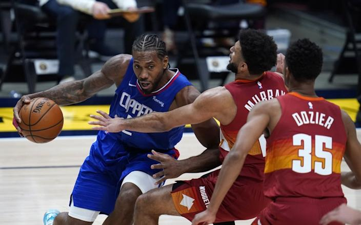 Los Angeles Clippers forward Kawhi Leonard, left, is defended by Denver Nuggets guards Jamal Murray.