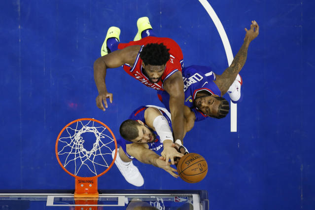 Philadelphia 76ers' Joel Embiid, top, leaps for a rebound against Los Angeles Clippers' Ivica Zubac, left, and Kawhi Leonard during the first half of an NBA basketball game, Tuesday, Feb. 11, 2020, in Philadelphia. (AP Photo/Matt Slocum)