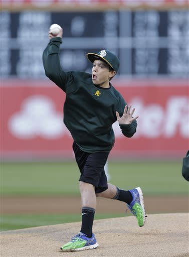 Aaron Hern, 12, from Martinez, Calif., who was injured in the Boston Marathon bombings, throws out the ceremonial first pitch before the Oakland Athletics' baseball game against the San Francisco Giants on Tuesday, May 28, 2013, in Oakland, Calif. Hern was released from Boston Children's Hospital on April 24. (AP Photo/Eric Risberg)