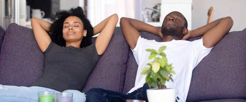 Black couple put hands behind head rest on sofa with closed eyes, taking a break