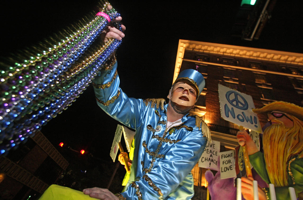 A reveler with the Mystic Stripers holds aloft a handful of beads for the crowds gathered on Royal Street in Mobile, Ala., Thursday, Feb. 16, 2012. The pre-Lenten blowout continues along the Gulf Coast culminating in Fat Tuesday celebrations Feb. 21. Tourism leaders estimate more than a million visitors pour into the Mobile area each Mardi Gras season to watch the festivities. (AP Photo/Mobile Register, G.M. Andrews) MAGS OUT; NO SALES
