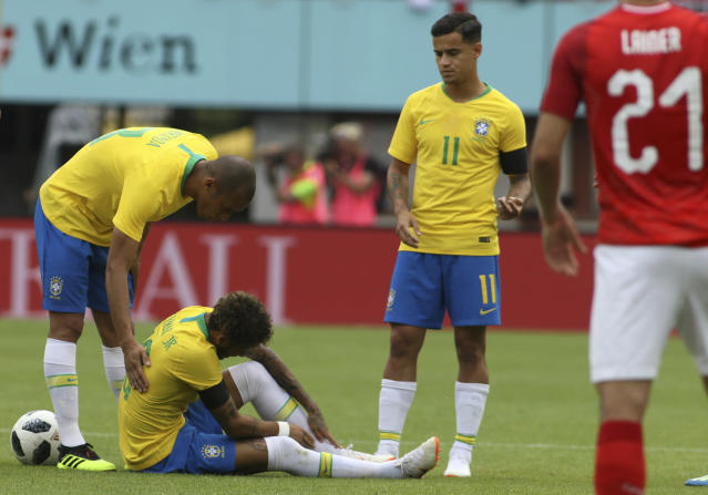Brazil's Neymar holding his ankle after a challenge with Austria's Julian Baumgartlinger during a friendly soccer match between Austria and Brazil at the Ernst Happel Stadium in Vienna, Austria, Sunday, June 10, 2018. (AP Photo/Ronald Zak)