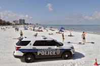 FILE - In this Monday, May 4, 2020 file photo, police officers patrol the area after Clearwater Beach officially reopened to the public in Clearwater Beach, Fla. Florida is among several states that amplified their 2021-2022 budgets with at least part of their share of a $195 billion state aid package from the recent American Rescue Plan Act signed by President Joe Biden. The state's record $101.5 billion budget is up roughly 11%, with bonuses for teachers, police and firefighters, and new construction projects at schools and colleges. (AP Photo/Chris O'Meara, File)