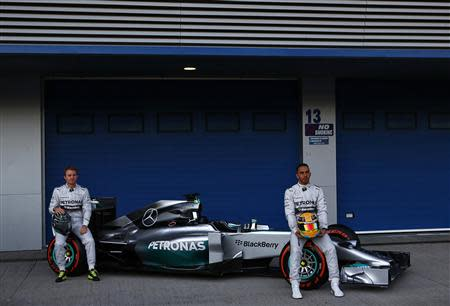 Mercedes Formula One racing driver Lewis Hamilton (R) of Britain and teammate Nico Rosberg of Germany unveil the new Mercedes F1 W05 car during its official presentation at the Jerez racetrack in southern Spain January 28, 2014. REUTERS/Marcelo del Pozo