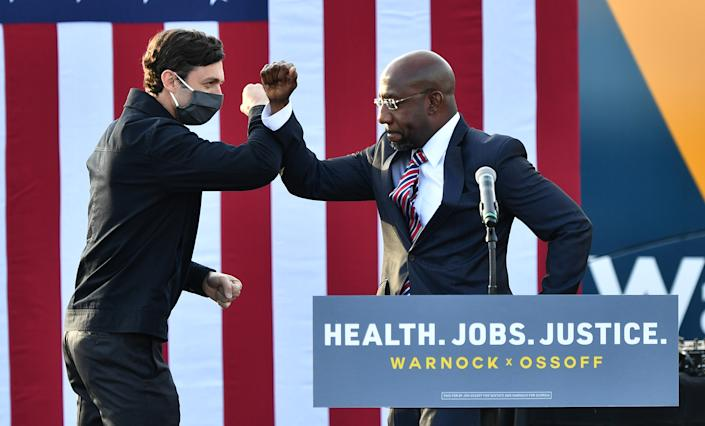 Georgia Democratic Senate candidates Jon Ossoff and Raphael Warnock greet each other onstage. (Photo by Paras Griffin/Getty Images)
