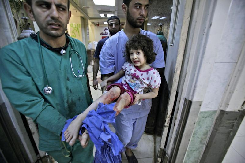 Medics carry Fatima Qassem, 6, whose legs were badly injured when government forces fired on her family's car, into the emergency room in a hospital in Aleppo, Syria, Tuesday, Sept. 11, 2012. (AP Photo/Muhammed Muheisen)