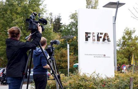 Members of the media film the FIFA logo outside their headquarters in Zurich