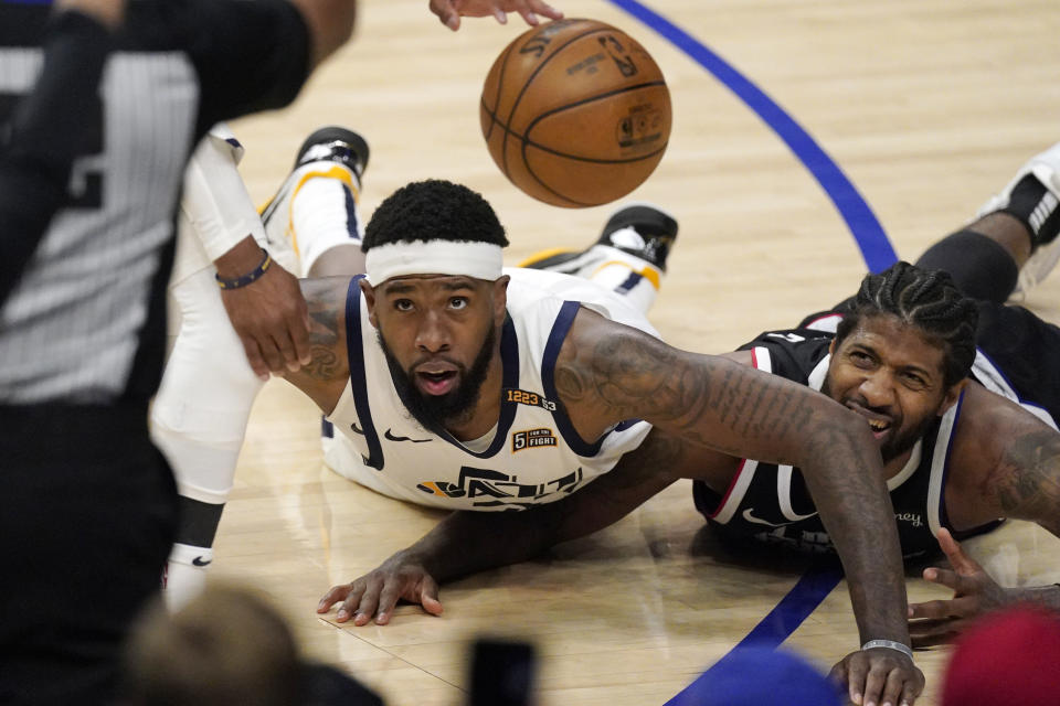 Utah Jazz forward Royce O'Neale, left, and Los Angeles Clippers guard Paul George go after a loose ball during the second half in Game 6 of a second-round NBA basketball playoff series Friday, June 18, 2021, in Los Angeles. (AP Photo/Mark J. Terrill)