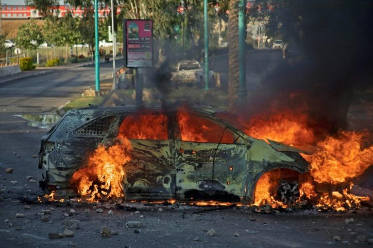 An Israeli police car burns after an Arab Israeli demonstration following the funeral of Mousa Hassouna in the central city of Lod near Tel Aviv on May 11