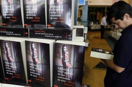 """A customer browses a copy of Swedish author Stieg Larsson's latest book,""""The Girl Who Kicked the Hornets' Nest"""", at a Madrid bookstore"""