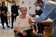 An elderly woman receives a vaccine against the coronavirus disease (COVID-19) at a nursing home in Athens