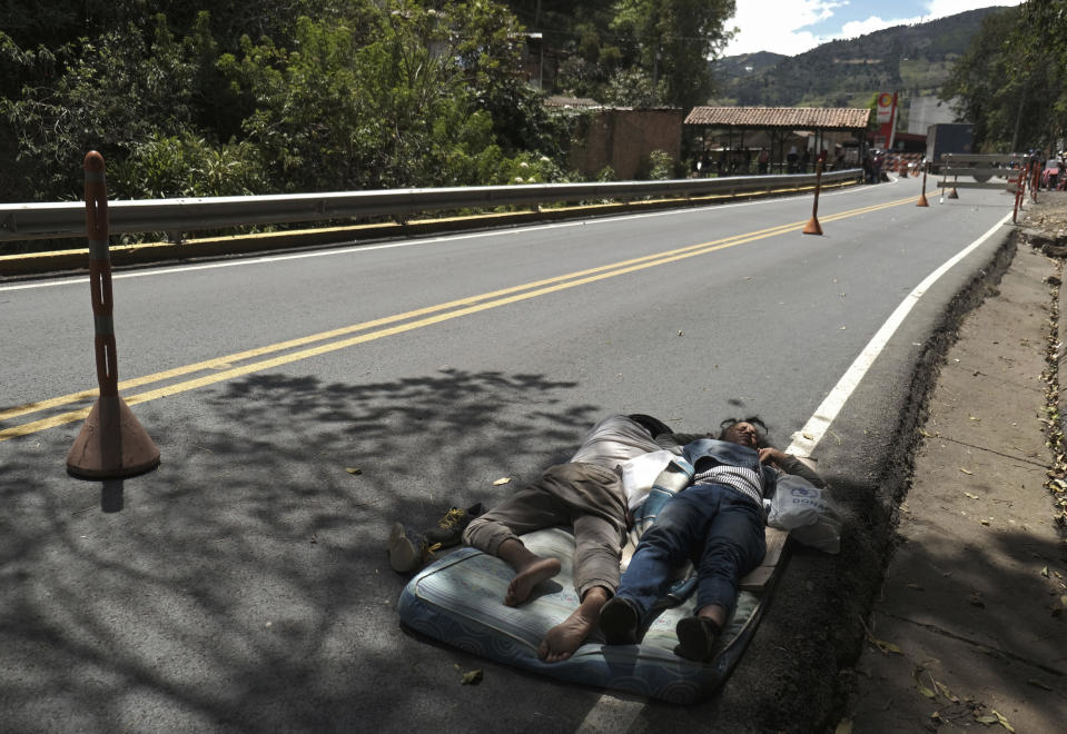 Venezuelan migrants sleep on a mattress on the side of the highway in Pamplona, Colombia, Wednesday, Oct. 7, 2020, a few hours away by car from the Venezuelan border. Once the migrants reach their destination, a new list of worries sets in: Colombia's unemployment rate rose from 12% in March to almost 16% in August; those who can't afford to pay rent are being evicted from their homes; and more than half of all Venezuelans in Colombia have no legal status. (AP Photo/Ferley Ospina)
