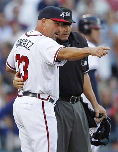 Atlanta Braves manager Fredi Gonzalez, left, speaks with an home plate umpire Jeff Kellogg after the Braves' Andrelton Simmons was ruled out at first base for interference during the fourth inning of the National League wild card playoff baseball game against the St. Louis Cardinals, Friday, Oct. 5, 2012, in Atlanta. (AP Photo/John Bazemore)