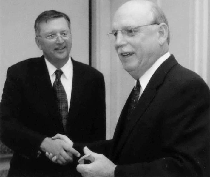 FILE - In this Sept. 20, 2005, file photo, Associated Press Vice President John Lumpkin, left, congratulates Little Rock Chief of Bureau Robert Shaw on the occasion of Shaw's 40th AP anniversary in Little Rock, Ark. Shaw, whose career of more than 40 years with The Associated Press included leading the coverage of news in three states as a bureau chief, died Thursday, July 15, 2021, in the Dallas suburb of Lewisville with family around him, said his daughter, Erin Moore. He was 79. (AP Photo/Danny Johnston, File)