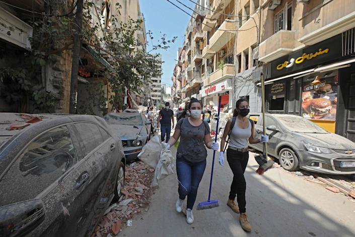 Volunteers carrying brooms and other equipment arrive on Gouraud street in the Gemmayze neighbourhood of Beirut, to clear debris on August 6, 2020, two days after a massive explosion shook the Lebanese capital: ANWAR AMRO / AFP