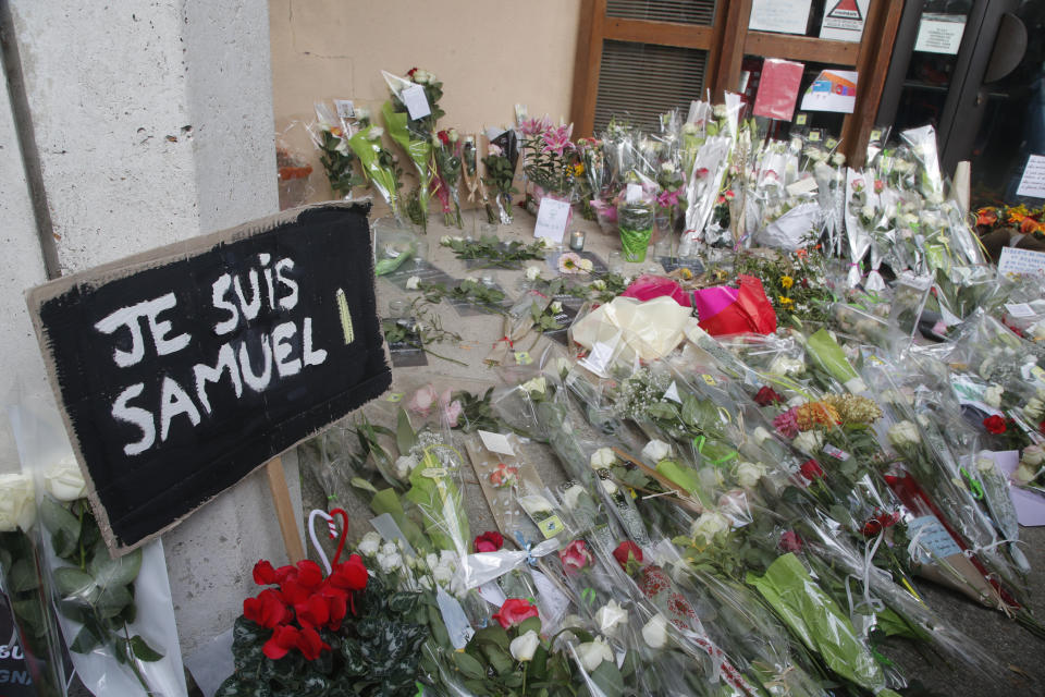 """A poster reading """"I am Samuel"""" and flowers lay outside the school where slain history teacher Samuel Paty was working. Source: AP"""