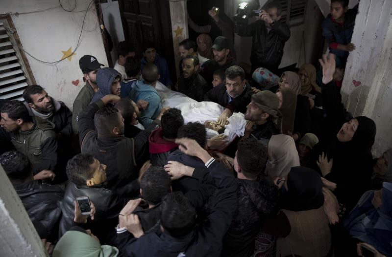 Relatives mourn over the body of 21-year-old Palestinian, Mohammed Saad, at the family home during his funeral in Gaza City, Saturday, March 30, 2019. Gaza's Health Ministry says Saad was shot dead by Israeli forces near the fence with Israel, hours before an expected mass protest there. (AP Photo/Khalil Hamra)