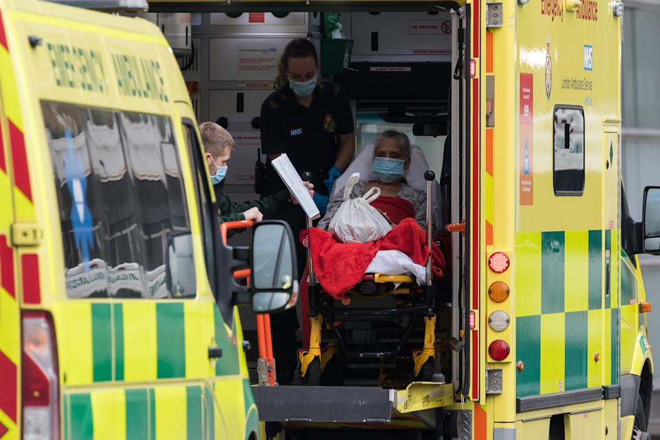 <p>Paramedics transport a patient in London</p> (Getty)