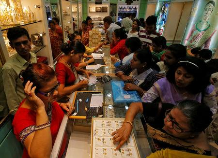 People buy gold ornaments at a jewellery showroom during Dhanteras, a Hindu festival associated with Lakshmi, the goddess of wealth, in Kolkata