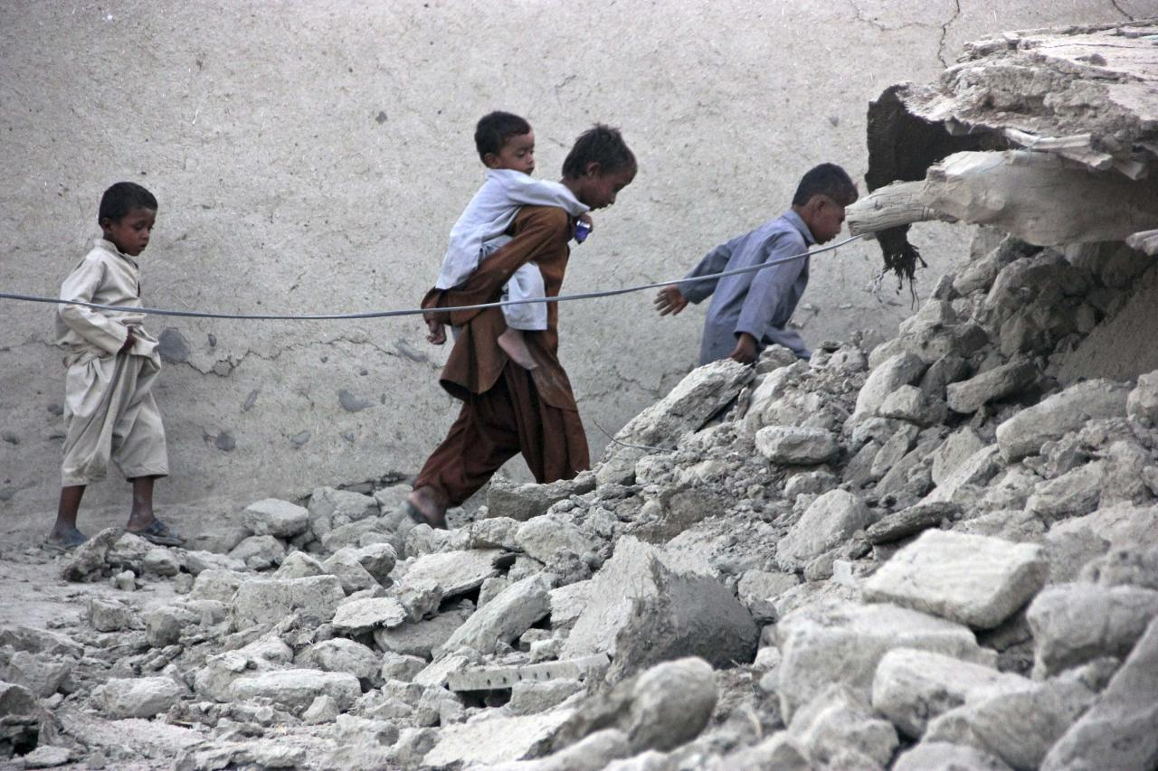 Survivors of an earthquake walk on rubble of a mud house after it collapsed following the quake in the town of Awaran, southwestern Pakistani province of Baluchistan, September 25, 2013. The death toll from a powerful earthquake in Pakistan rose to at least 208 on Wednesday after hundreds of mud houses collapsed on people in a remote area near the Iranian border, officials said. REUTERS/Sallah Jan (PAKISTAN - Tags: DISASTER TPX IMAGES OF THE DAY)