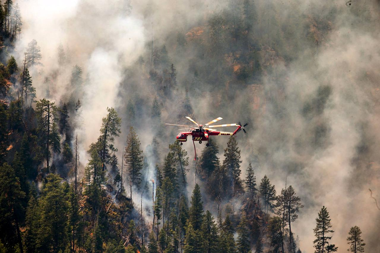 Helicopters drop water on part of the Slide Fire in Sterling Canyon at the Oak Creek Overlook above Sedona, Ariz. on Thursday, May 22, 2014. Hundreds of firefighters worked Thursday to protect communities on the edge of Flagstaff from a wildfire that is chewing up a scenic Arizona canyon with towering flames and burning entire trees down to nothing but ash. (AP Photo/The Arizona Republic, Michael Schennum) MARICOPA COUNTY OUT; MAGS OUT; NO SALES