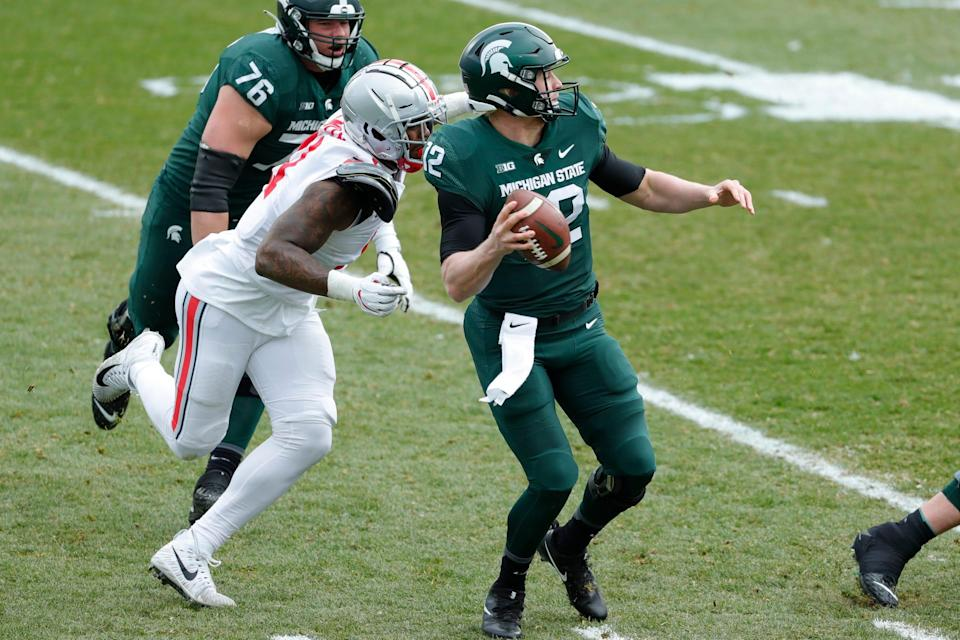 Michigan State quarterback Rocky Lombardi is sacked by Ohio State defensive end Tyreke Smith during the first half at Spartan Stadium in East Lansing, Saturday, Dec. 5, 2020.