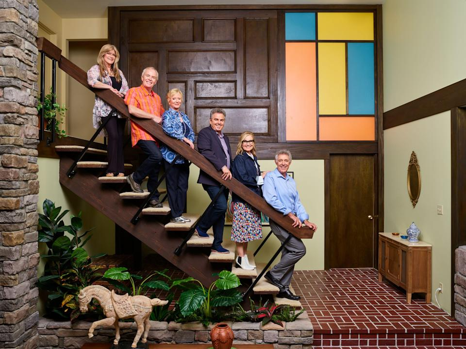 The 'Brady Bunch' actors recreate their iconic pose on the famous Brady house staircase. (Photo: HGTV)