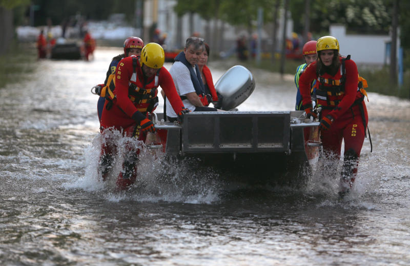 In this picture made available Sunday June 9, 2013, rescuers evacuate inhabitants in Magdeburg, eastern Germany, Saturday June 8, 2013. Thousands of people have been evacuated from their homes in a region of eastern Germany where the Elbe river has flooded and burst through a dam, officials said Sunday. More than 20 people have been killed by a week of flooding in central Europe, as rivers such as the Danube, the Elbe and the Vlatava have overflowed after heavy rains and caused extensive damage in central and southern Germany, the Czech Republic, Austria, Slovakia and Hungary. (AP Photo/dpa, Jens Buettner)