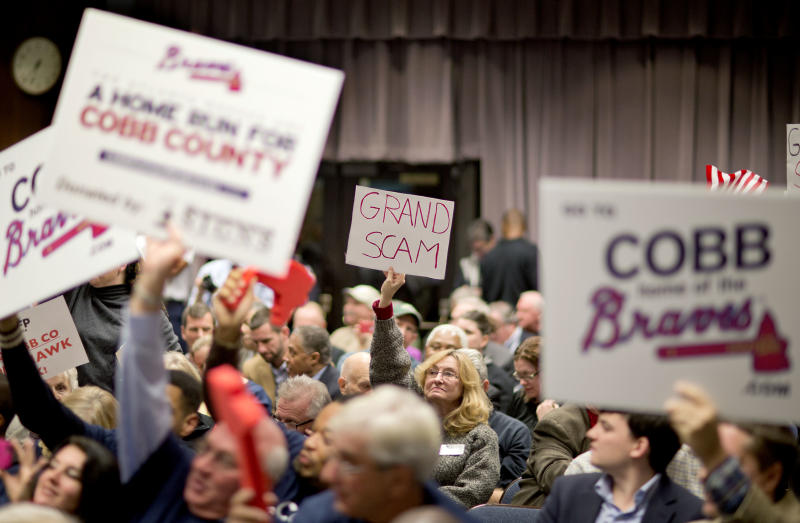 FILE- In this Nov. 26, 2013 file photo, proponents and opponents of a plan for the Atlanta Braves to build a new baseball stadium in Cobb County hold up their respective signs before the start of a Cobb County commission hearing on the subject, in Marietta, Ga. A deal for hundreds of millions of dollars in public money to draw the Atlanta Braves north of their downtown home is pitting conservative tea party activists against the elected and civic leaders in the staunch Republican county, with opponents saying the use of public money to help a private business is not what American capitalism should be about. (AP Photo/David Goldman, File)
