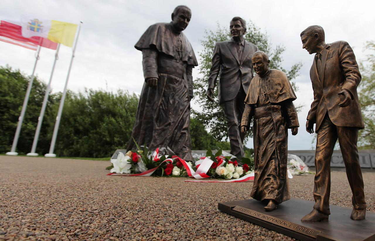 A miniature stands in front of the new statue of former President Ronald Reagan and Pope John Paul II that was unveiled in Gdansk, Poland, on Saturday, July 14, 2012. The statue honors the two men whom many Poles credit with helping to topple communism. (AP Photo/Czarek Sokolowski)